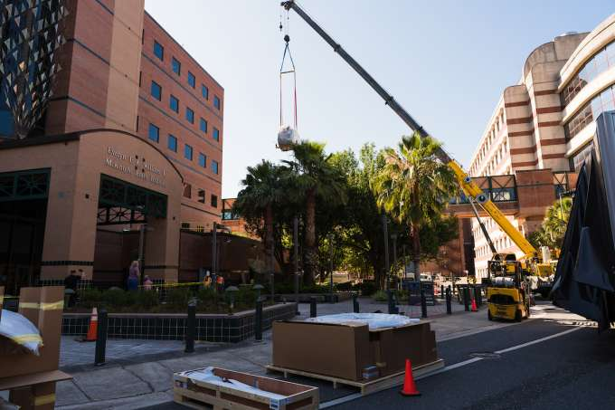 Crane lifting scanner nearly to 3rd floor of MBI building
