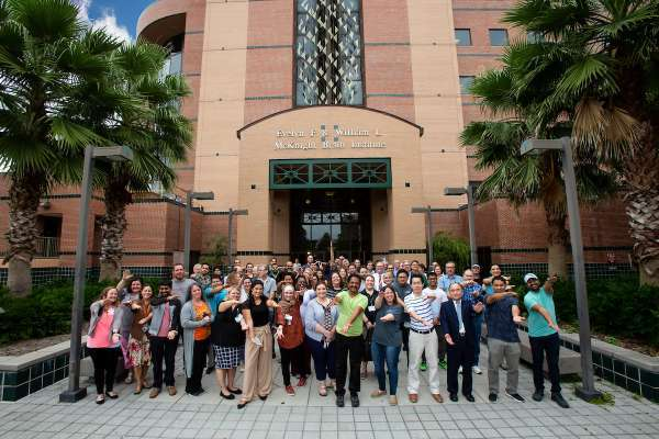 Staff doing a gator chop signal with their arms outside the M-B-I building